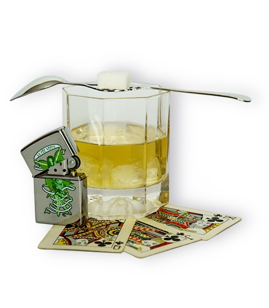 Versage glass with absinthe drink, absinthe spoon and sugar. Zippo lighter with Green Fairy design.